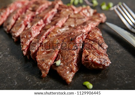 Thick Slices of Hot Grilled Whole Machete Steak or Skirt Steak on Black Stone Background. Fresh Juicy Medium Rare Beef Grillsteak. Barbecue Meat Top View Close Up