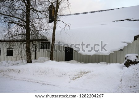 Thick snow hanging on the house roof after winter heavy snowfall. #1282204267