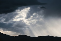 thick stormy clouds over the mountains with intense sun rays peaking through and contrasty light shot in Tasmania, Australia in winter