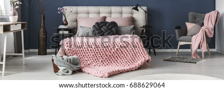 Thick wool pink blanket on cozy bed in stylish bedroom