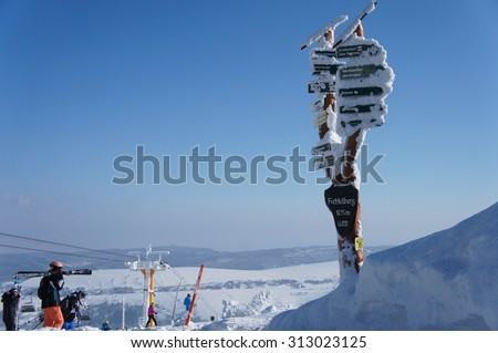 thickly snow-covered and frost-covered signposts on the Fichtelberg in the Ore Mountains in Saxony, Germany, overlooking the Bohemian part of the Erzgebirge in the Czech Republic/Signposts in winter