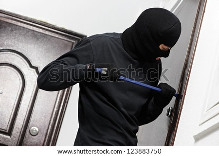 Thief Burglar opening metal door with a crowbar during house breaking