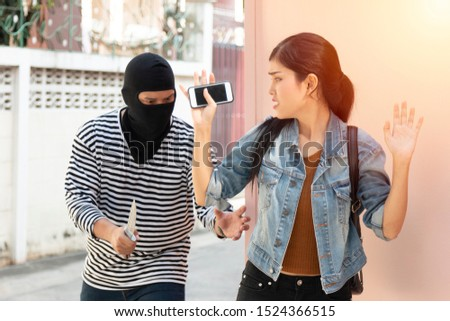 Thief dangerous man or robber in black and white shirt with masked threatening to steal items from the victim.The female victim giving valuables in fear.