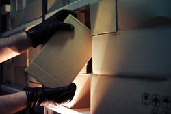 Thief hands with gloves steal a box of goods in a warehouse in the dark. Concept of problems with theft of goods and postal parcels