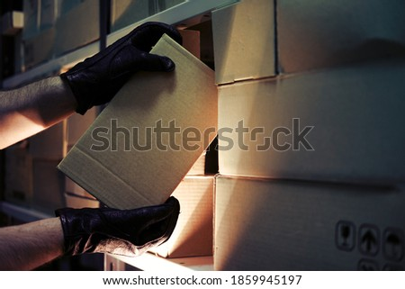 Thief hands with gloves steal a box of goods in a warehouse in the dark. Concept of problems with theft of goods and postal parcels Foto stock ©