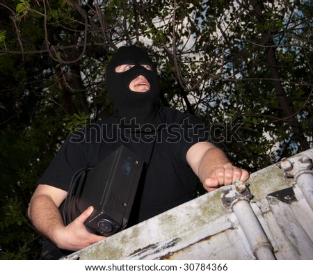 Thief in a mask with device in hands climbs through a fence