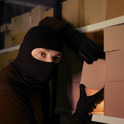 Thief in black balaclava steals with a parcel in a warehouse in the dark. Concept of security problems in warehouses and stores