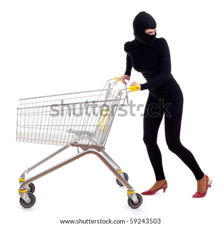 thief in black clothes and balaclava with shopping cart - stock photo