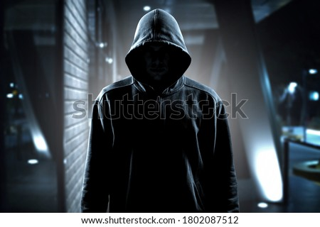 Thief in black clothes on room background Foto stock ©