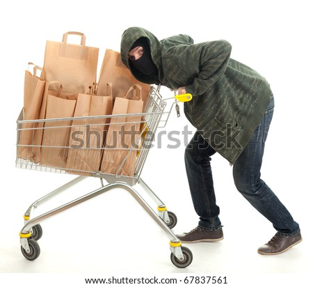 thief in dark clothes and balaclava with shopping cart full of papers bags