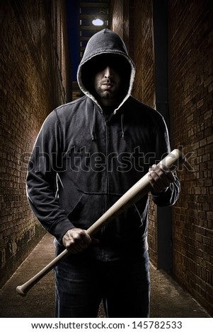Thief in the hood on a dark alley