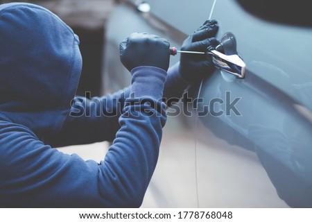 thief using a tool to break into a car. Zdjęcia stock ©