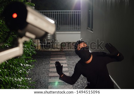 Photo of  Thief wearing black suit with balaclava and glove being caught by CCTV, surveillance camera during sneak into a house at night