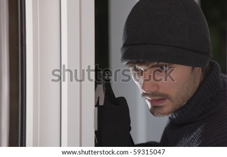 thief with crowbar breaking into a house by night