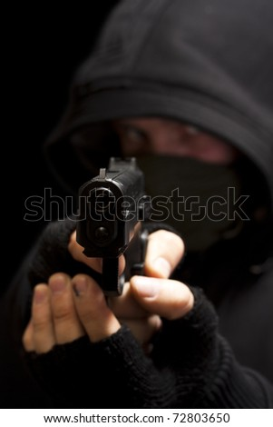 Thief with gun aiming into a camera - isolated on black background