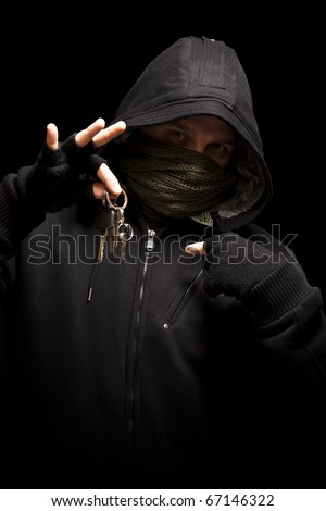 Thief with keys aiming into a camera - isolated on black background