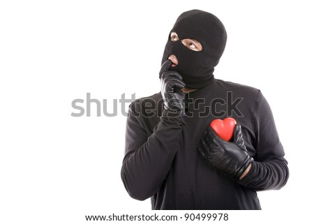 Thief with mask and holding a heart with an expression of love - stock photo