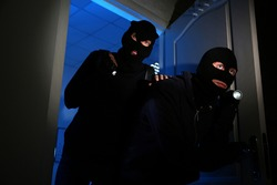Thieves with flashlights breaking into house at night