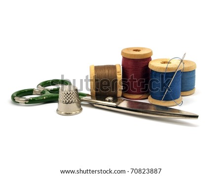 thimble, needle, scissors and threads on white background