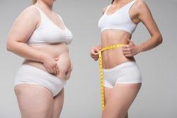 Thin girl measuring her abdomen near fat one