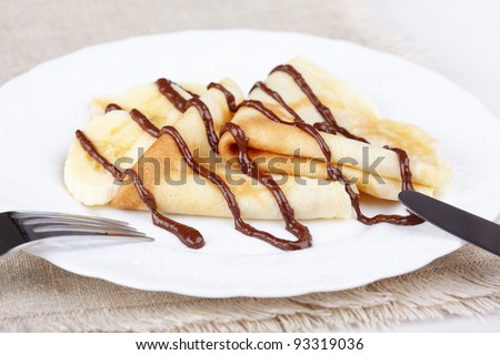 Thin pancakes with banana and chocolate