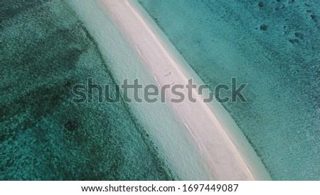 Thin sandbar in the middle of the sea. The elongated sandbar is a luxurious hangout, a coconut drink in one hand and dried octopus in another!