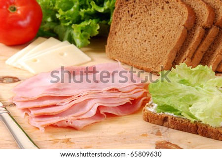 Thin sliced deli ham being made into a sandwich