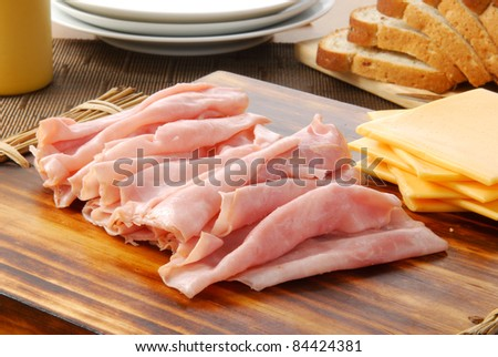 Thin sliced ham, cheddar cheese and a loaf of bread