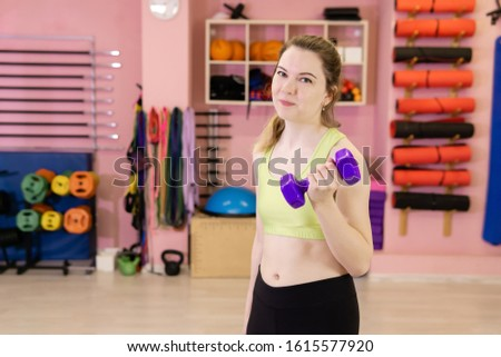 thin young woman who has recently started exercising is engaged in the gym, starts exercises with dumbbells