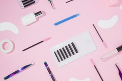 Things for the work of lash-makers, artificial eyelashes, microbrachis, glue, tweezers, combs, brushes for eyelash extensions. Eyelash extension, painting of eyebrows. Top view, pink background.