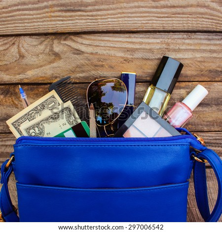 Things from open lady handbag. women\'s purse on wood background. Cosmetics, money and women\'s accessories fell out of the blue handbag.