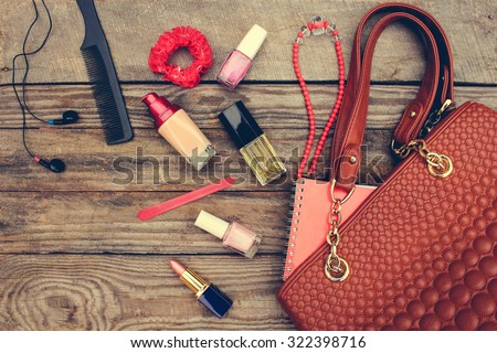 Things from open lady handbag. women\'s purse on wood background. Toned image.