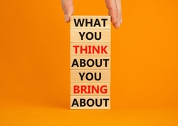 Think about bring about symbol. Wooden blocks with words What you think about you bring about. Beautiful orange background. Businessman hand. Business, motivational think or bring concept. Copy space.