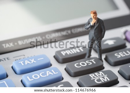 Think about cost concept. Business figurine stand on calculator near cost button.