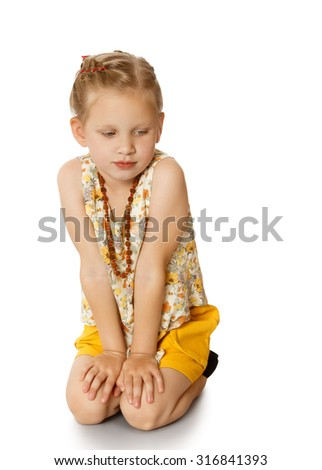 Think and think fashionable girl sitting on knees and looks down.neck girls long beads-Isolated on white background