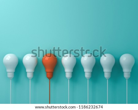 Think different concept One hanging orange light bulb standing out from the white light bulbs on blue pastel color  wall background leadership and individuality creative idea concepts 3D rendering
