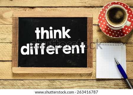Think different on blackboard. Think different On blackboard with cup of coffee, notebook and pen on wooden background