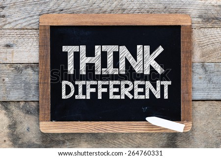 Think different Sign. Think different Sign on blackboard on wooden background #264760331