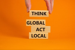 Think global act local symbol. Wooden blocks form the words 'Think global act local' on beautiful orange background. Male hand. Beautiful background. Business and think global act local concept.