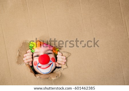 Think outside the box. Funny kid clown looking through hole on cardboard. Child playing at home. 1 April Fool's day concept. Copy space for your text.