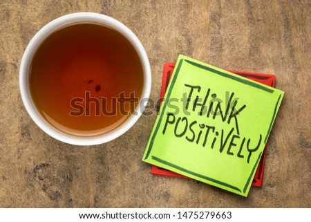 think positively motivational reminder - handwriting on a sticky note with a cup of tea