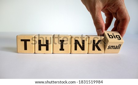Think small or think big. Hand flips a cube and changes the words 'think small' to 'think big' or vice versa. Beautiful white background. Business concept. Copy space.