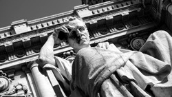thinker statue in front of the Palazzo della Cassazione in Rome, bottom view with blue sky. copy space