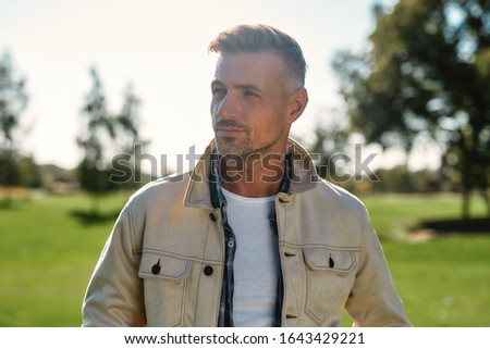 Thinking about life. Portrait of handsome and stylish bearded man looking away while standing in the middle of the park. Nature concept. Beautiful people