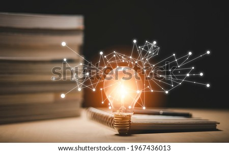 Thinking and creative concept, Light bulb on the Book and light bulb style bokeh vintage dark background,Concept The idea of reading books, knowledge, and searching for new ideas.