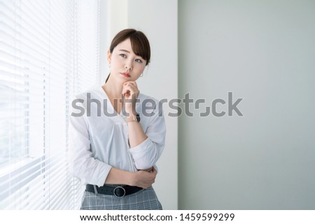 Thinking attractive asian woman in office.