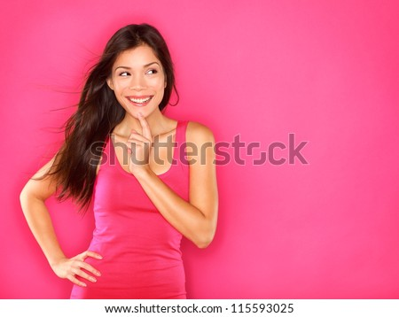 Thinking beautiful young woman looking to the side at pink copyspace. Funky fresh and playful multiracial Asian Chinese / Caucasian smiling happy and joyful on pink background.