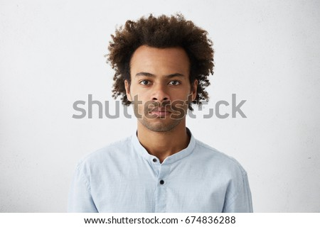 Thinking black Afro American man with serious expression looking with dark narrow eyes directly into camera while posing against white studio wall. Grave businessman in shirt thinking about work