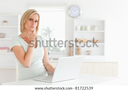 Thinking blonde woman looking at notebook in the kitchen