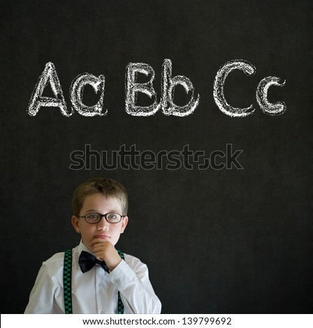 Thinking boy dressed up as business man with learn English language alphabet on blackboard background